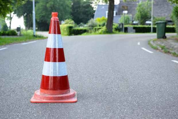 red and white traffic cone on road
